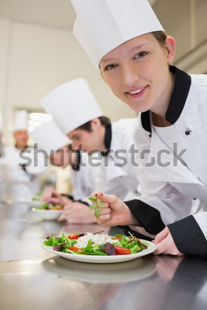Happy chef looking up from preparing salad in culinary class Stock photo © wavebreak_media