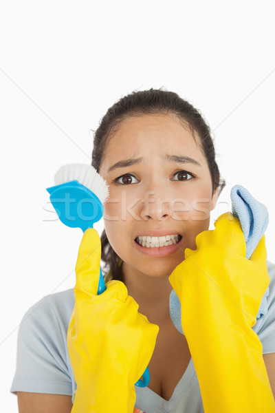 Stressed woman holding scrubbing brush and rag wearing rubber gloves Stock photo © wavebreak_media