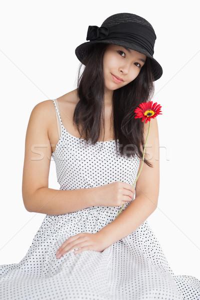 Woman holding flower in a polka dot dress on white background  Stock photo © wavebreak_media