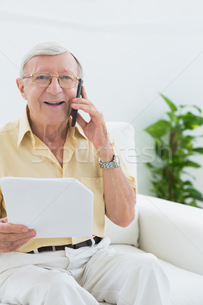 пожилого улыбаясь человека чтение документы телефон Сток-фото © wavebreak_media