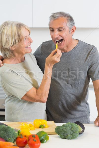 Husband tasting a slice of yellow pepper Stock photo © wavebreak_media