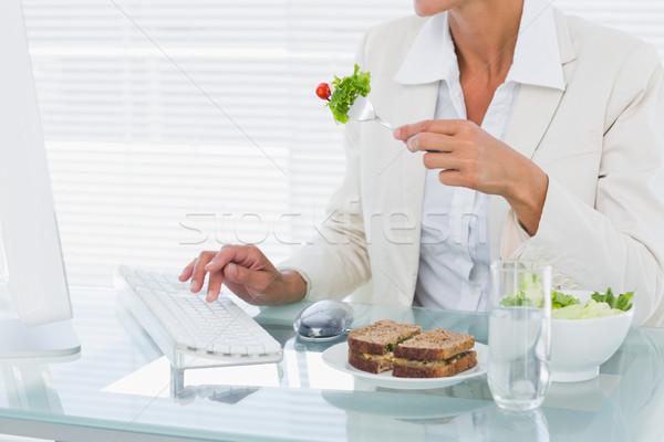 üzletasszony számítógéphasználat eszik saláta asztal középső rész Stock fotó © wavebreak_media