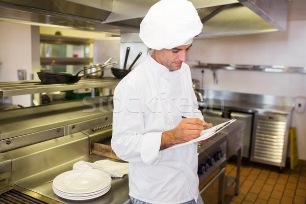 Concentrado masculina cocinar escrito portapapeles cocina Foto stock © wavebreak_media
