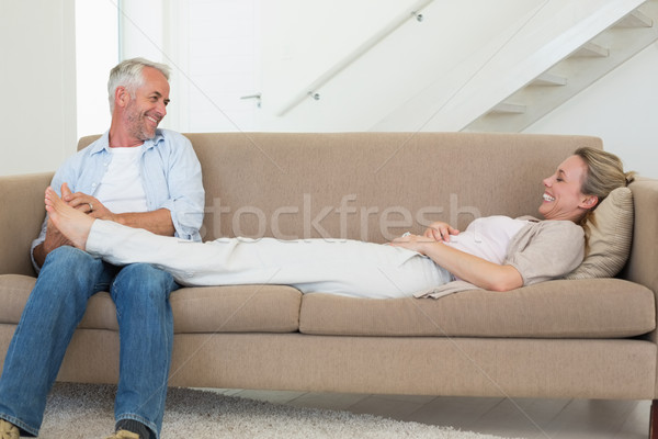Caring man giving his partner a foot rub on the couch Stock photo © wavebreak_media