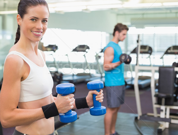 Fit brunette exercising with blue dumbbells Stock photo © wavebreak_media