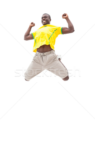 Happy brazilian football fan jumping up Stock photo © wavebreak_media