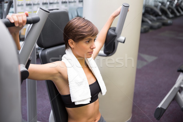 Serious brunette using weights machine for arms Stock photo © wavebreak_media