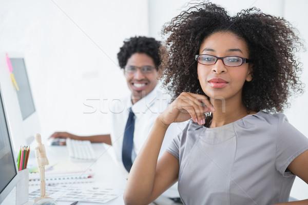 Young editor smiling at camera at her desk Stock photo © wavebreak_media