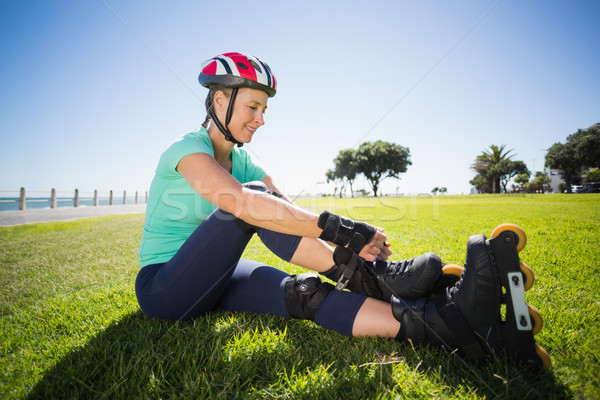 Fit mature woman tying her roller blades on the grass Stock photo © wavebreak_media