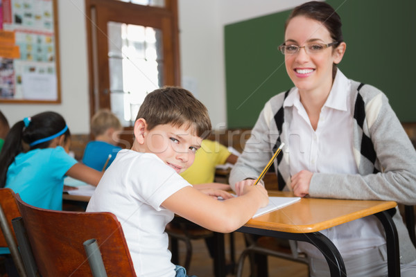 Pretty teacher helping pupil in classroom smiling at camera Stock photo © wavebreak_media