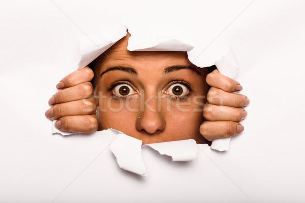 Young woman looking through paper rip Stock photo © wavebreak_media