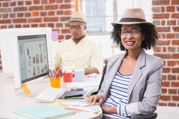 Smiling female photo editor at office desk Stock photo © wavebreak_media