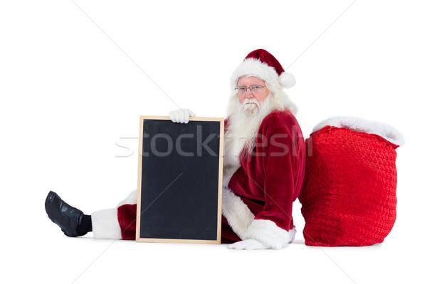 Santa sits leaned on his bag with a board Stock photo © wavebreak_media