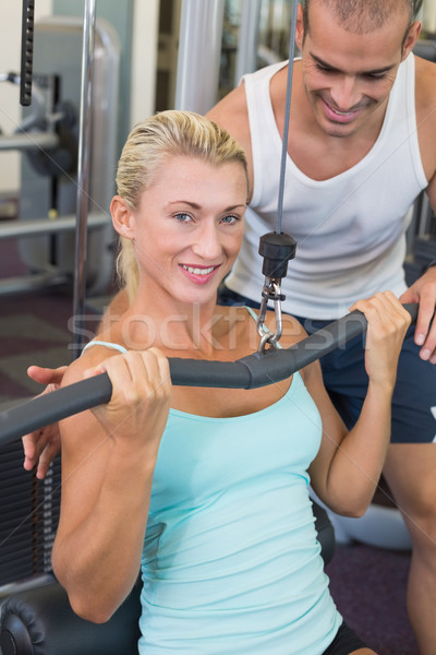 Male trainer assisting beautiful young woman on lat machine Stock photo © wavebreak_media