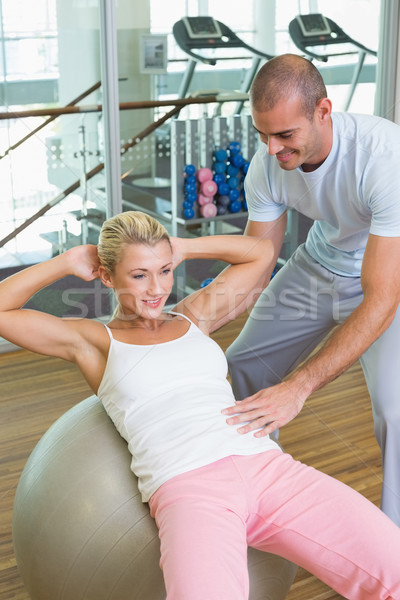 Trainer assisting woman with abdominal crunches at gym Stock photo © wavebreak_media