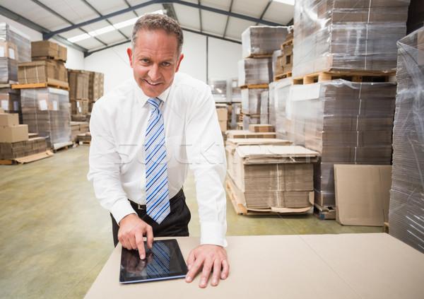 Smiling boss using tablet pc Stock photo © wavebreak_media