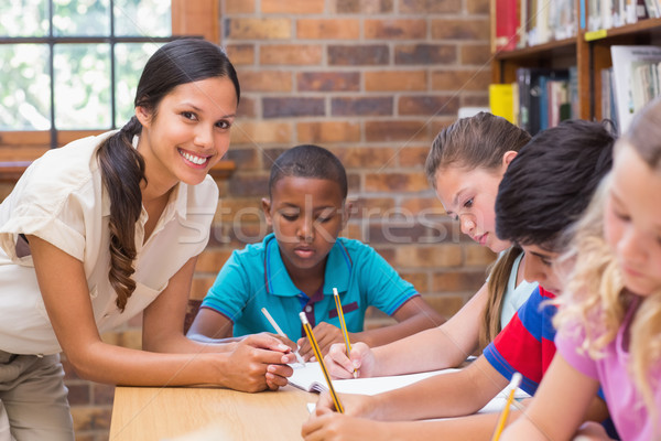 Stock photo: Pretty teacher helping pupils in library