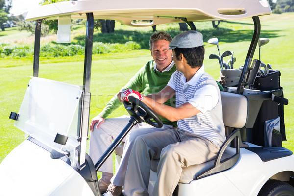 Golfing friends driving in their golf buggy  Stock photo © wavebreak_media