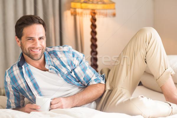 Bel homme détente lit boisson chaude maison chambre Photo stock © wavebreak_media