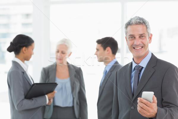 бизнесмен смартфон коллеги за служба портрет Сток-фото © wavebreak_media
