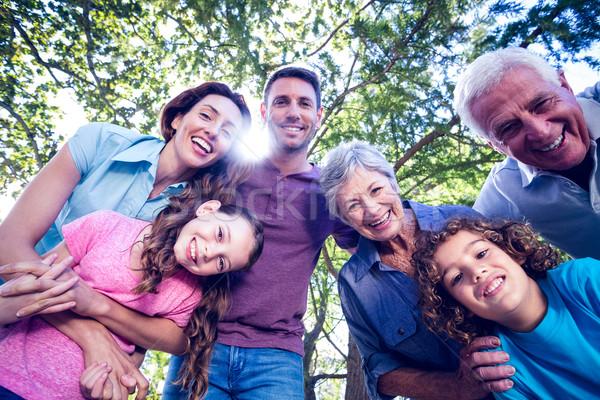 Boldog család mosolyog kamera napos idő lány fa Stock fotó © wavebreak_media