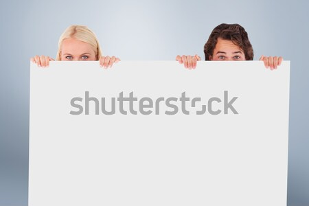 Young couple hiding behind a blank sign Stock photo © wavebreak_media