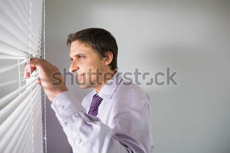 Stock photo: Businesswoman looking out the blinds