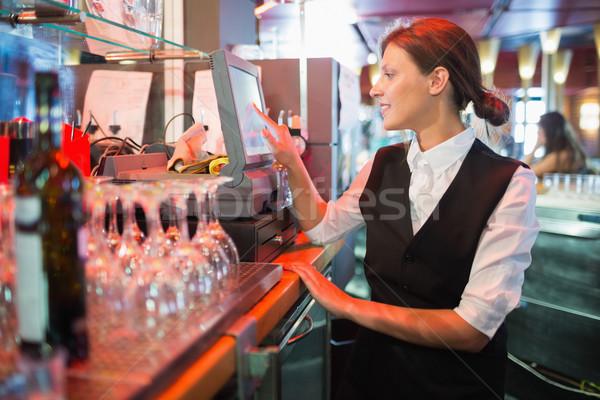 Happy barmaid using touchscreen till Stock photo © wavebreak_media