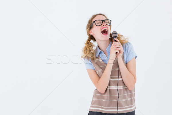 Geeky hipster woman singing into a microphone  Stock photo © wavebreak_media
