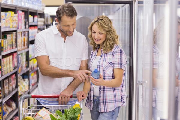 Sorridente casual casal olhando garrafa de água supermercado Foto stock © wavebreak_media