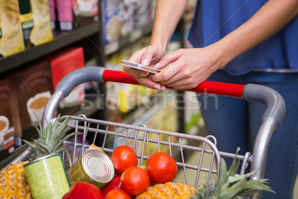 Pretty woman pushing trolley in aisle and texting  Stock photo © wavebreak_media