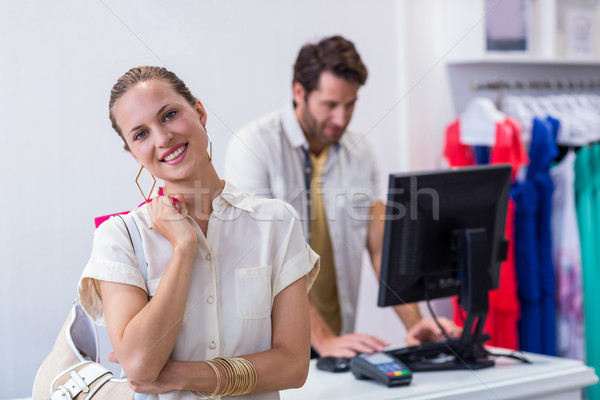 Stock photo: Smiling woman standing in front of till