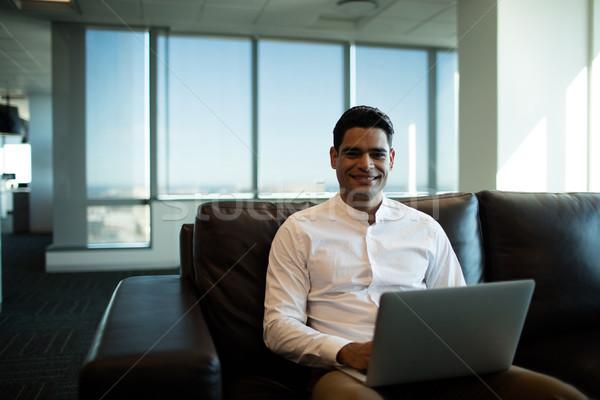 бизнесмен используя ноутбук сидят диван служба портрет Сток-фото © wavebreak_media