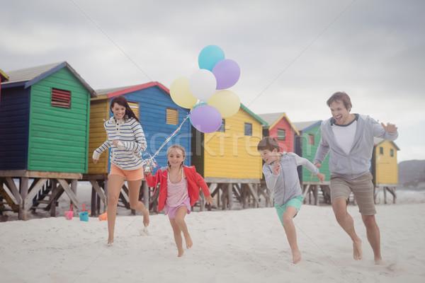Boldog család tart léggömbök fut tengerpart homok Stock fotó © wavebreak_media