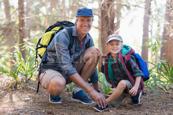 Portrait of father tying shoelace for son in forest Stock photo © wavebreak_media