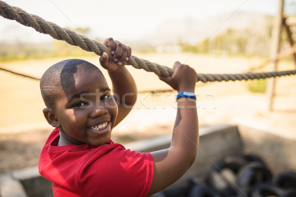 Stock photo: Portrait of happy boy crossing the rope during obstacle course