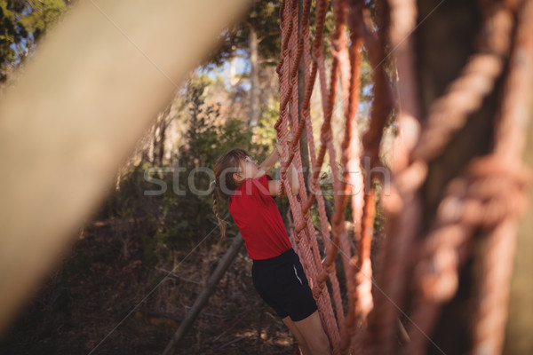 Girl climbing a net during obstacle course Stock photo © wavebreak_media