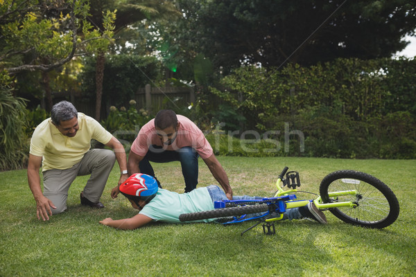 Stock photo: Grandfather and father helping fallen boy with bicycle