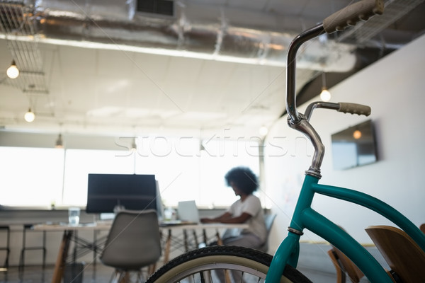 Close-up of bicycle with man working in background at office Stock photo © wavebreak_media