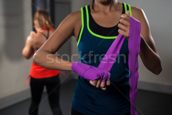 Woman tying hand wrap on hand Stock photo © wavebreak_media