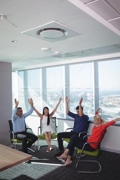 Derűs üzletemberek karok a magasban iroda ül székek Stock fotó © wavebreak_media