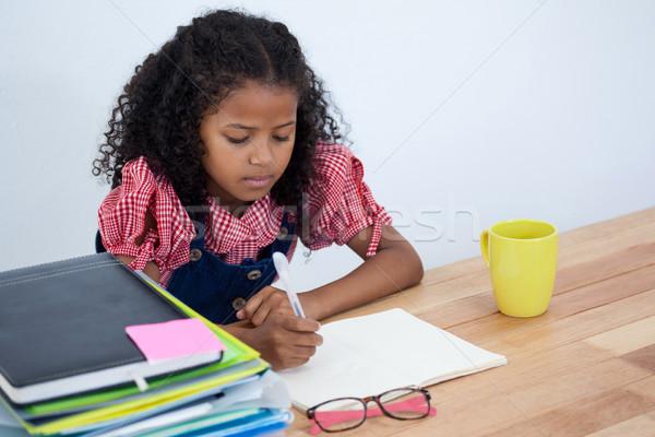 Girl imitating as businesswoman writing on book Stock photo © wavebreak_media