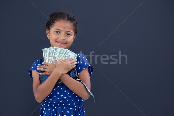 Portrait of smiling girl embracing currency Stock photo © wavebreak_media