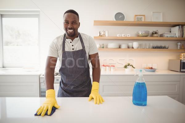 Smiling man cleaning the kitchen worktop Stock photo © wavebreak_media