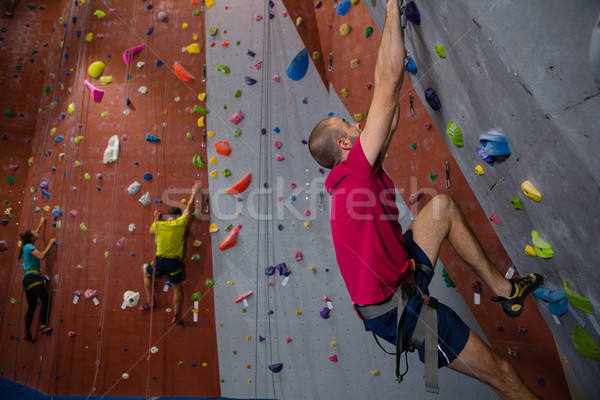 Confident athletes and trainer climbing wall in club Stock photo © wavebreak_media