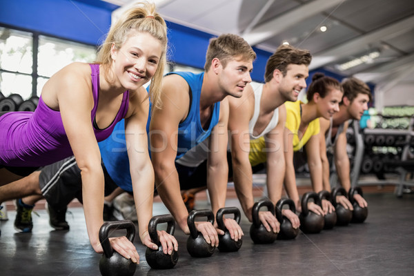 Fitness class in plank position with dumbbells Stock photo © wavebreak_media
