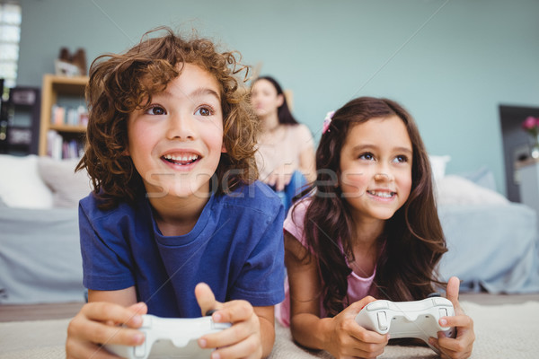 Close-up of happy siblings with controllers playing video game Stock photo © wavebreak_media