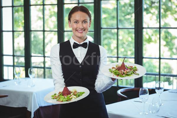 Souriant serveuse plaques restaurant heureux Photo stock © wavebreak_media