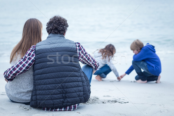 Parents sitting while looking at children on beach  Stock photo © wavebreak_media