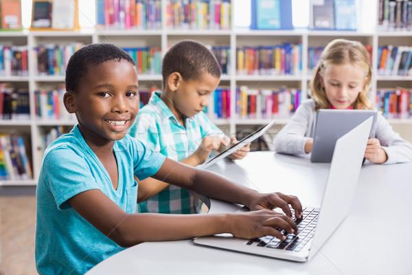 Enfants utilisant un ordinateur portable numérique comprimé bibliothèque école Photo stock © wavebreak_media